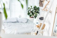 Bed in cozy bedroom. Bed with white bedding in cozy bedroom interior stock photos
