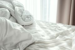 Bed with white crumpled sheet and blanket in the morning sun rays. Selective focus stock photo