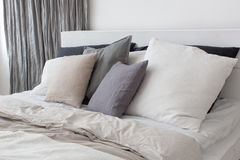 Bed with white and grey linens. And a lot of pillows Stock Images