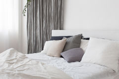 Bed with white and grey linens. And a lot of pillows Stock Photography