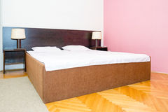 Bed with  white sheets and pillows with two bedside lamp on the Stock Photo