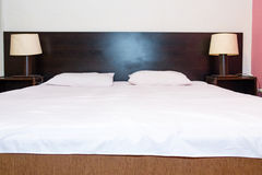 Bed with  white sheets and pillows with two bedside lamp on the Royalty Free Stock Photos