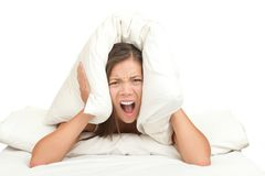 Bed woman noise - funny. Bed woman covering ears with pillow because of noise. Funny image isolated on white background royalty free stock photos