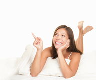 Bed woman pointing up Stock Photo