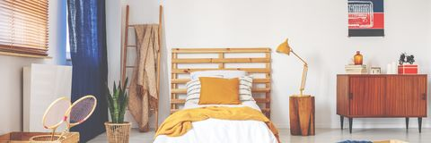 Bed with wooden bedhead, white sheets, ochre cushion and yellow knit blanket. In real photo of white teenager room interior with vintage cupboard, ladder with royalty free stock photography