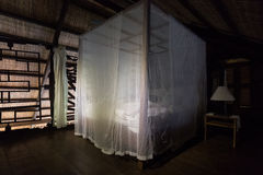 A bed in a wooden lodge with a mosquito net Stock Image