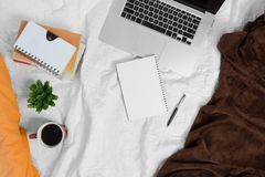 Bed workspace with coffee notebook and laptop. Coffee,laptop, potted plant and pile of books on bed. Bed workspace Stock Photos