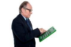 Bedachtes schauendes Leitprogramm, das an einem Taschenrechner arbeitet Stockbilder