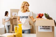 Bedachtzame heldere vrouw die de voedselpakketten controleren stock afbeeldingen