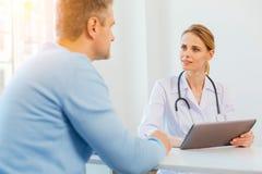 Bedachtzame vrouwelijke arts die aan patiënt luisteren stock afbeelding