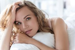 Bedachtzame vrouwelijke persoon plaatsbepaling op beddegoed royalty-vrije stock fotografie