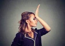 Bedauern schaden dem Handeln Traurige Frau, die Hand auf dem Kopf schlagend, der duh Moment lokalisiert auf grauem Hintergrund ha lizenzfreie stockfotografie