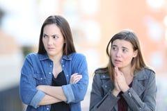 Bedauerndes Mädchen, das um Verzeihen zu ihrem verärgerten Freund bittet lizenzfreie stockbilder