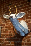 Bedazzled Deer Head Wall mounted. White bedazzled with Christmas lights deer head mounted on a brick wall. taxidermy Stock Photo