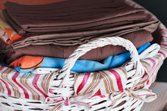 Bedclothes of different colors in wicker basket on light background. Bedclothes different colors in wicker basket on light background stock photo