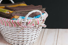 Bedclothes of different colors in wicker basket on light background. Bedclothes different colors in wicker basket on light background royalty free stock photography