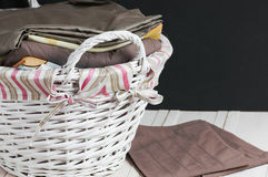 Bedclothes of different colors in wicker basket on light background. Bedclothes different colors in wicker basket on light background royalty free stock image