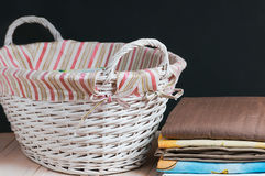Bedclothes of different colors in wicker basket on light background. Bedclothes different colors in wicker basket on light background royalty free stock photo