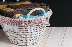 Bedclothes of different colors in wicker basket on light background. Bedclothes different colors in wicker basket on light background stock images