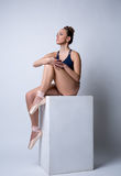 Beddable ballerina sitting on cube in studio Royalty Free Stock Photos