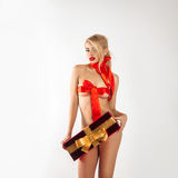 Beddable blonde girl with a bow on the chest and big gift Royalty Free Stock Image