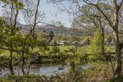 Beddgelert, Wales, the UK - a view through some trees. This image shows a view of Beddgelert, North Wales, the UK. It was taken on a bright, sunny day in spring Stock Image