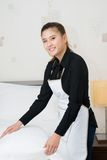 Bedding in the apartment. Vertical portrait of a young chambermaid bedding in the apartment Royalty Free Stock Photo