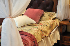 Bedding and curtain. Red and yellow color bedding, pillow and white curtain, shown as comfortable home environment and furniture Stock Photo
