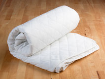 Bedding sheet. Roll of white bedding sheet on wooden background Royalty Free Stock Photos