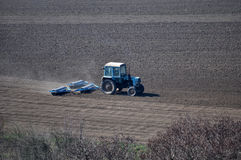 Bedding spring crops_8. Track rollers with tractor prepares soil for planting spring crops Stock Photos