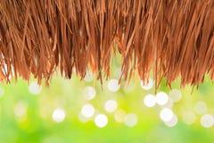 Bedecken Sie die Dächer mit Gras, mit Stroh gedeckt, auf grünem Bokeh-Hintergrund Stockbilder