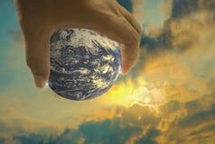 Bedecken Sie, in einer Handvoll, glänzende Sonne, mit dem Abendhimmel ist das backgroun mit Erde stock abbildung