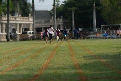 Bedecken Sie Läuferbahn mit Unschärfe zurück von Athleten mit Gras stockbilder