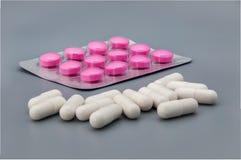 Bedecken Sie mit roten Pillen hinter zerstreuten weißen Pillen auf einem grauen Hintergrund mit Blasen stockfoto