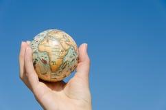 Bedecken Sie vorbildliche Palme der Kugel auf blauem Hintergrund, Afrika mit Erde Lizenzfreie Stockfotos