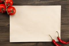 Bedecken Sie Weinlesepapier mit Tomaten und Chile-Pfeffer alterten hölzernen Hintergrund Gesunde vegetarische Nahrung Rezept, Men Stockbild