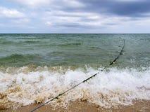 Bedeckt mit Meerespflanzenbojenseil durch eine brechende Welle auf einem sandigen Strand Schwarzen Meers, Primorsko, Bulgarien lizenzfreies stockbild