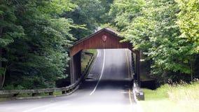 Bedeckte Holzbrücke hinunter eine Landstraße mit Bäumen im Sommer Stockbilder