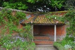 Bedeckte Nische Seat in ummauertem Garten an Mottisfont-Abtei, Hampshire, England Stockbild