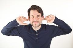 Bedeckungsohren des jungen Mannes von den lauten Geräuschen, lokalisiert auf weißem backg Stockbilder