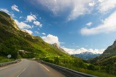 Bedekte twee steegweg die bergen en bos in toneel alpien landschap en humeurige hemel kruisen Panorama van auto opgezette camera Stock Afbeeldingen