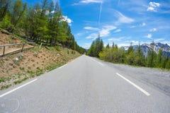 Bedekte twee steegweg die bergen en bos in toneel alpien landschap en humeurige hemel kruisen Panorama van auto opgezette camera Royalty-vrije Stock Foto's
