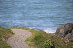 Bedekte wegwinden rond kustuitzicht Stock Afbeeldingen