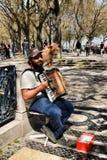 Bedelaar die de harmonika spelen die met zijn hond bedelen stock fotografie