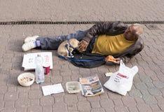 Bedelaar met hond op de straat Stock Foto's