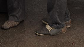 Bedelaar in oude vuile schoenen stock videobeelden