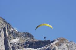 Bedeutungs-Segelflugzeug, das vom Schweizer Berg springt. Lizenzfreies Stockbild