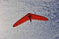 Bedeutungsgleitenmann auf einem orange Flügel im Himmel lizenzfreie stockbilder