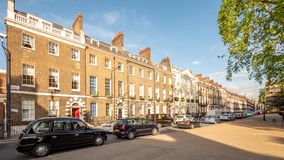 Bedford Square town houses and traffic, Bloomsbury, London. LONDON, UK - 17 MAY 2018: A terraced row of grand Georgian town houses in Bedford Square, Bloomsbury stock photos