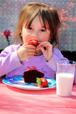 Bedhead Breakfast. A little girl with bedhead enjoys her breakfast of strawberries, a muffin and milk outside early in the morning. Shallow depth of field Royalty Free Stock Image